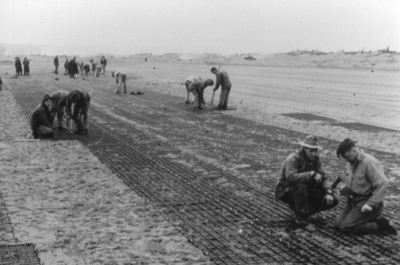 Laying steel mesh runway on the beach